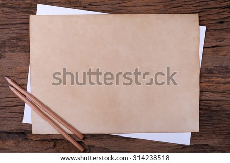 Old paper with  pencil on wooden table - stock photo
