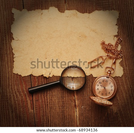 old paper with pocket watch and magnifying glass on wood background