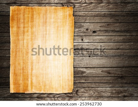 old papyrus paper on wooden background - stock photo