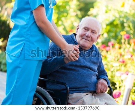 Old patient sitting in wheelchair, holding the doctor's hand. - stock photo