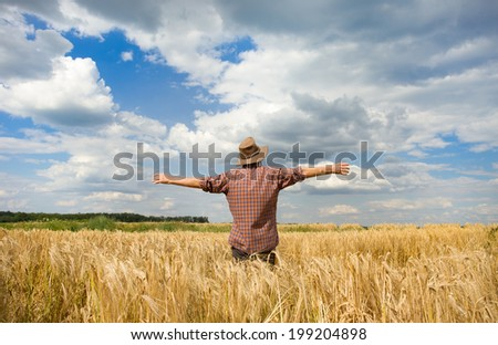Old peasant standing with open arms on wheat field - stock photo