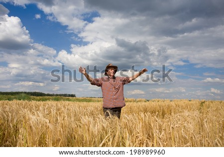 Old peasant standing with open arms on wheat field and feeling happy - stock photo