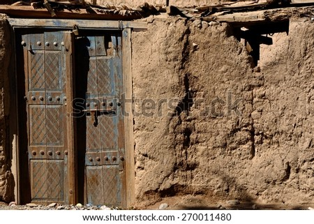 Old peeled blue door on a village mud house in Oman