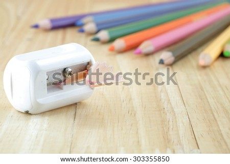 Old pencil sharpener and color pencils on wooden table - stock photo