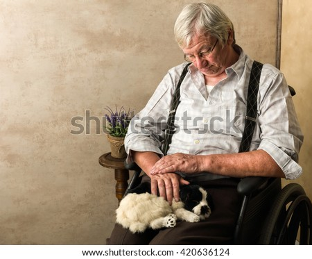 Old pensioner in nursing home sleeping with his dog on his lap - stock photo