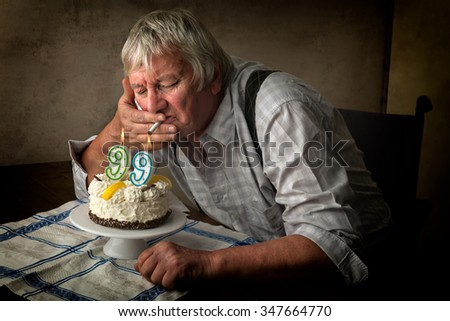 Old pensioner lighting his cigarette on his birthday cake. - stock photo