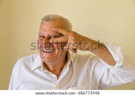 Old pensioner showing rock gesture isolated on yellow wall background