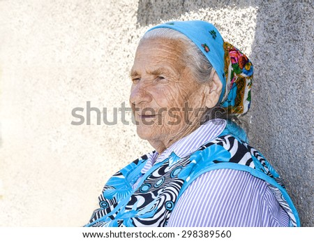 Old pensive grandmother at a kerchief on a gray background - stock photo