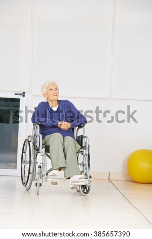 Old pensive woman sitting in wheelchair and looking up in a nursing home - stock photo