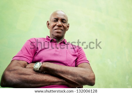 Old people and emotions, portrait of senior african american man looking and smiling at camera with arms crossed. Copy space, low angle view, - stock photo