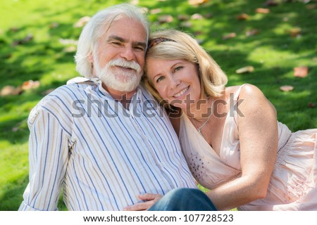 Old people and romance, elderly husband and wife in love, lying on grass in park