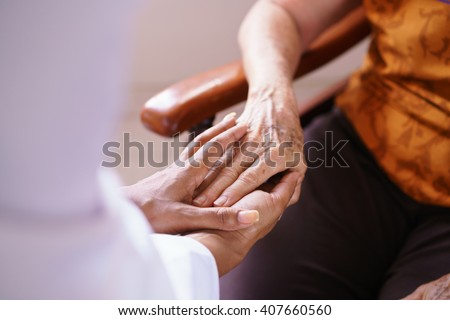 Old people in geriatric hospice: Black doctor visiting an aged patient, holding hands of a senior woman. Concept of comfort and compassion - stock photo