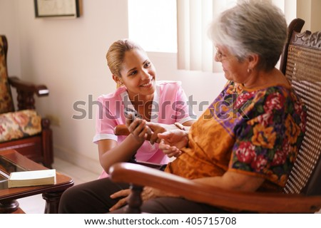 Old people in geriatric hospice: elderly lady having eyesight problems viewing the screen of mobile phone. A nurse helps the senior woman dialing a number on the tiny keyboard  - stock photo