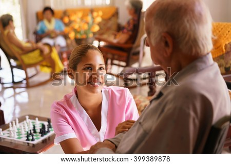 Old people in geriatric hospice: young attractive hispanic woman working as nurse takes care of a senior man on wheelchair. She talks with him then goes away to help other patients - stock photo