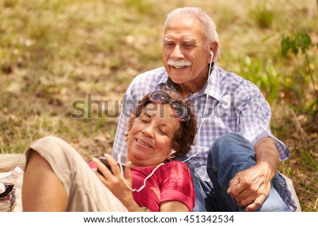 Old people, senior couple, elderly man and woman in park. Grandpa and grandma listening to song, music with mp3 player - stock photo