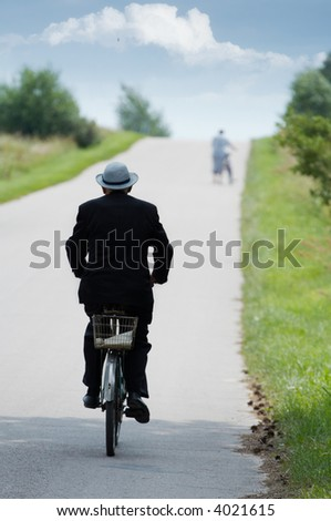 Old person in suit and hat riding a vintage bicycle. - stock photo