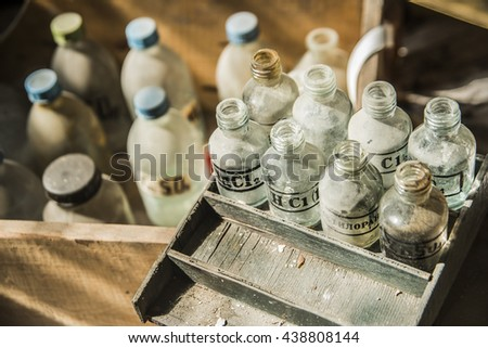 old pharmacy bottles covered with dust in pharmaceutical laboratory in wooden old box. ZnSO4, MgCl2, acid and a metal salt.  - stock photo