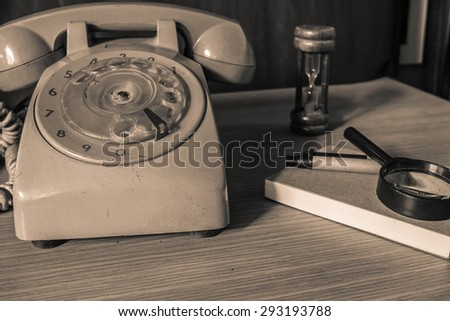 Old phone and stationery on a wooden table.