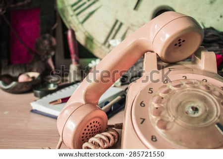 Old phone on a wooden table vintage. - stock photo