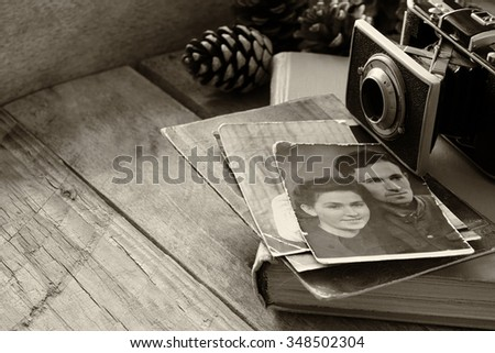 old photo camera, antique photos and old book on wooden table. black and white. selective focus - stock photo