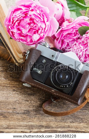 old  photo camera with books and peony flowers - stock photo