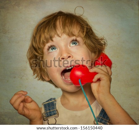 Old photo: child with a red phone  - stock photo