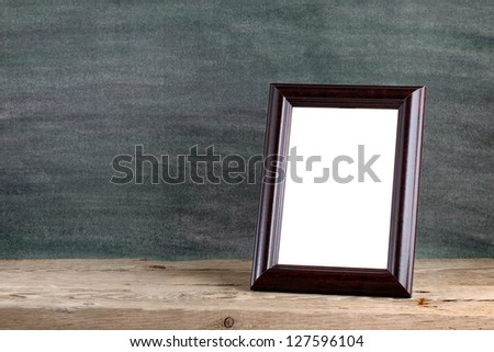 Old photo frame on wooden table - stock photo