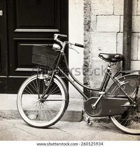 Old photo of bicycle with wicker basket, Italy - stock photo