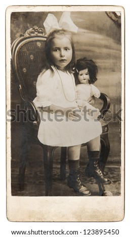 old photo of little girl with doll toy. nostalgic vintage picture from ca. 1900 - stock photo