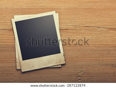 Old photo paper on vintage wood background - stock photo