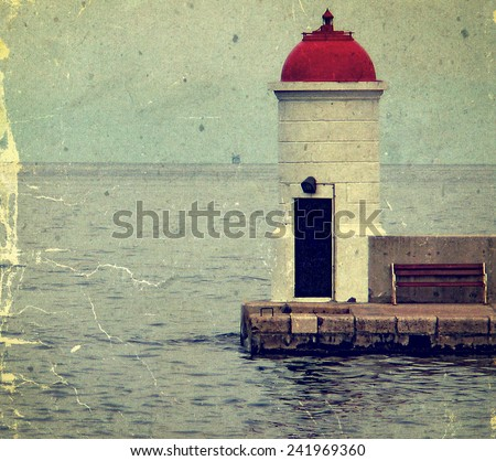 Old photo with lighthouse from Zadar, Croatia, situated at the end of a pier with bench rest. - stock photo