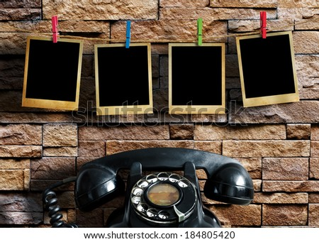 Old picture frame hanging on clothesline and old telephone on grunge background. - stock photo