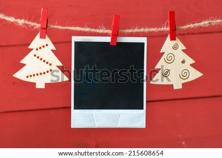 Old pictures on wood background with Christmas decoration.Wooden christmas tree hanging with old picture on rope - stock photo