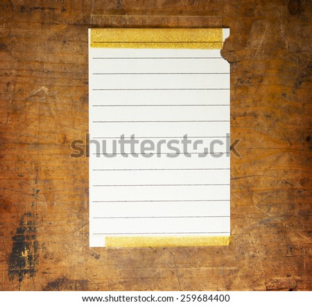 Old piece of blank scrap paper with lines, taped to an old grungy wooden wall or surface.  - stock photo