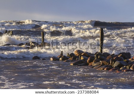 Old pier and stormy weather with breaking waves - stock photo