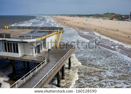 Old pier at Scheveningen long, sandy beach by the North Sea, view from above, South Holland, the Netherlands. - stock photo