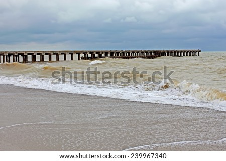 Old pier during stormy weather. Black Sea, Novofedorivka, Crimea, Ukraine. Sea water mixed with sand and colored in yellow - stock photo