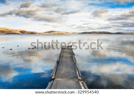 Old pier on the lake, a floating flock of ducks and the sky reflecting in the water. Autumn landscape with lake and mountains views