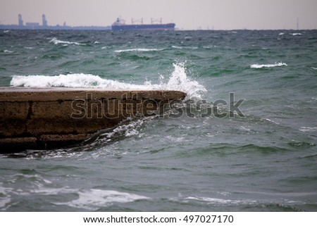 old pier with Powerful sea splash wave with sprays and foam  with vessel on the background