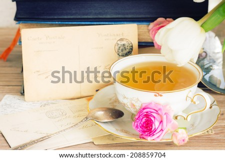 old pile of  mail with antique cup of tea - stock photo