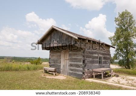 Old pioneer log cabin in rural Iowa - stock photo