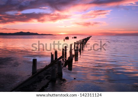 Old pipeline running out into the Great Salt Lake at sunset, Utah, USA. - stock photo