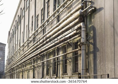 Old pipes on the wall outside of an old abandoned factory. - stock photo