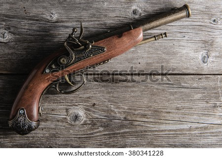 old pistol  on the wooden board - stock photo