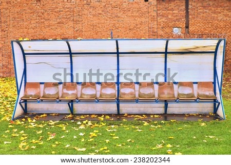 Old plastic seats on outdoor stadium players bench, chairs with worn paint below yellow roof.  Autumn leaves, end of football season. - stock photo
