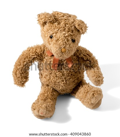 Old plush brown teddy bear sitting on a white background with shadow facing the camera