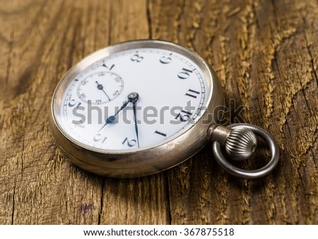 Old pocket watch and key on the wooden background with blank space - stock photo