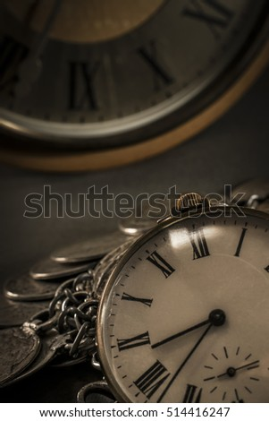 Old pocket watch in dark environment with coin jewelers and old wall clock in background