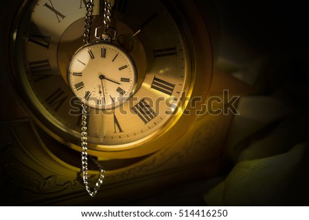 Old pocket watch in dark environment with old wall clock in background