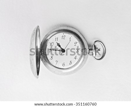 Old pocket watch on a textural light background. - stock photo